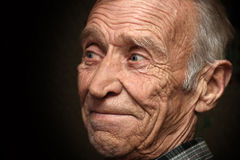 Uomo anziano allegro su un fondo nero Fotografia Stock