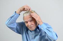 Uomo anziano attivo che pettina i suoi capelli con un pettine Fotografia Stock Libera da Diritti
