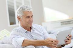 Uomo anziano bello che per mezzo della compressa Fotografia Stock Libera da Diritti