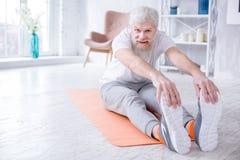 Uomo anziano bello che piegano in avanti e dita del piede commoventi Immagini Stock