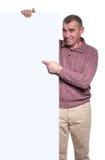 Uomo anziano casuale felice che indica il suo dito il bordo in bianco Fotografia Stock Libera da Diritti