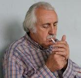 Uomo anziano che alleggerisce una sigaretta Fotografie Stock Libere da Diritti