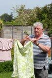 Uomo anziano che appende fuori il lavaggio. Fotografia Stock