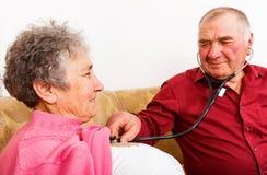 Uomo anziano che ascolta il suo battito cardiaco della moglie immagine stock libera da diritti