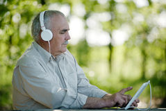 Uomo anziano che ascolta la musica su una compressa Fotografie Stock