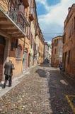 Uomo anziano che cammina dal vicolo nel centro urbano di Ferrara Immagine Stock