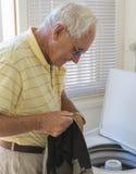 Uomo anziano che controlla i vestiti in lavanderia Immagini Stock Libere da Diritti