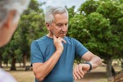Uomo anziano che controlla impulso dopo avere corso immagini stock