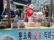 Uomo anziano che cucina per la gente sulla via nel mercato del myeongdong di CHU immagini stock