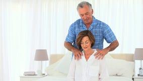 Uomo anziano che dà alla sua moglie un massaggio archivi video