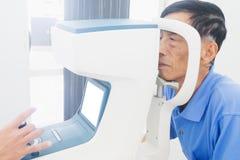 Uomo anziano che fa gli occhi dei hes esaminare da un oculista su uno strumento di prove in clinica moderna fotografia stock