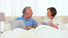 Uomo anziano che lavora al suo computer mentre la sua moglie sta leggendo stock footage
