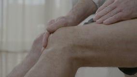 Uomo anziano che massaggia il suo ginocchio artritico che ha dolore unito a casa - archivi video
