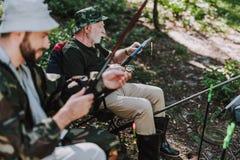 Uomo anziano che mette esca sul gancio mentre pescando immagini stock