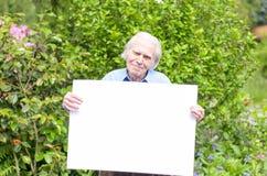 Uomo anziano che mostra una lavagna in bianco Fotografie Stock
