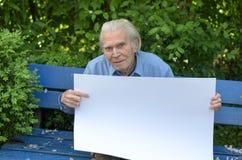 Uomo anziano che mostra una lavagna in bianco Fotografia Stock