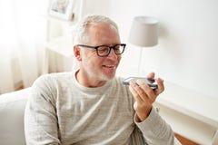 Uomo anziano che per mezzo del registratore di comando di voce sullo smartphone fotografia stock