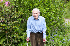 Uomo anziano che per mezzo delle grucce dell'avambraccio per camminare Immagini Stock