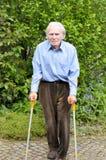 Uomo anziano che per mezzo delle grucce dell'avambraccio per camminare Immagine Stock