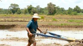 Uomo anziano che per mezzo di piccolo trattore per arare l'azienda agricola per registrare il suolo per ottenere piantare video d archivio
