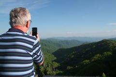 Uomo anziano che prende un'immagine delle montagne con il suo telefono cellulare Fotografie Stock Libere da Diritti