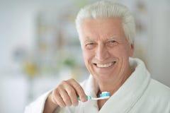 Uomo anziano che pulisce i suoi denti fotografia stock
