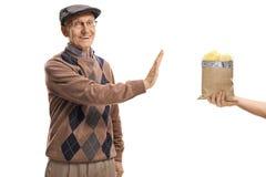 Uomo anziano che rifiuta una borsa dei chip fotografia stock libera da diritti