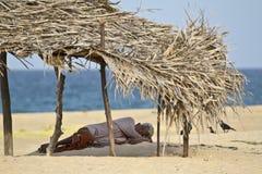 Uomo anziano che riposa nell'ombra nella spiaggia, Batticaloa, Sri Lanka fotografia stock libera da diritti