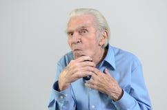 Uomo anziano che si rade con un rasoio elettrico senza cordone Fotografia Stock Libera da Diritti