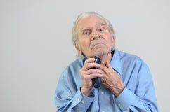 Uomo anziano che si rade con un rasoio elettrico senza cordone Immagini Stock Libere da Diritti