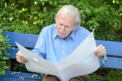 Uomo anziano che si siede da solo su un banco nel parco Fotografie Stock Libere da Diritti