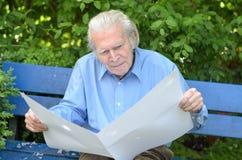 Uomo anziano che si siede da solo su un banco nel parco Immagine Stock