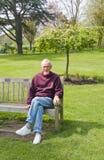 Uomo anziano che si siede sul banco in sosta fotografia stock