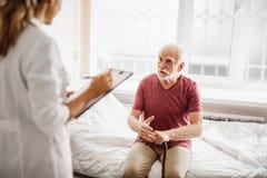 Uomo anziano che si siede sul letto di ospedale e che ha conversazione con medico immagini stock libere da diritti
