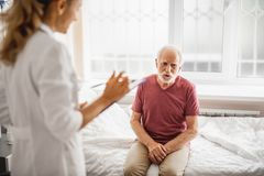 Uomo anziano che si siede sul letto di ospedale e che parla con medico fotografia stock
