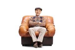 Uomo anziano che si siede in una poltrona di cuoio Fotografie Stock Libere da Diritti