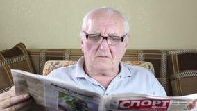 Uomo anziano che si siede in una sedia e che legge un giornale video d archivio