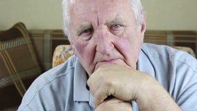 Uomo anziano che si siede in una sedia e che tiene una canna in sue mani archivi video
