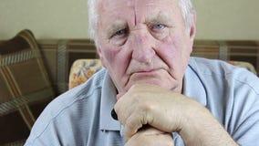 Uomo anziano che si siede in una sedia e che tiene una canna in sue mani stock footage