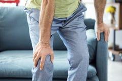 Uomo anziano che soffre dal dolore del ginocchio fotografia stock