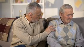 Uomo anziano che sostiene amico turbato, sedentesi sul sofà a casa, problemi sanitari video d archivio