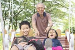 Uomo anziano che spinge i suoi nipoti sull'oscillazione Fotografie Stock Libere da Diritti