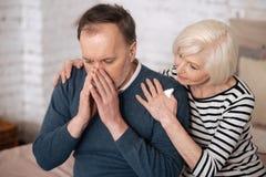 Uomo anziano che starnutisce vicino alla moglie Immagine Stock Libera da Diritti