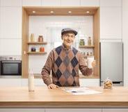 Uomo anziano che tiene un bicchiere di latte e che sta dietro un contatore di legno in una cucina immagini stock