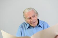 Uomo anziano che tiene un grande strato di carta ocraceo in bianco Fotografia Stock Libera da Diritti