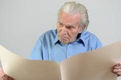 Uomo anziano che tiene un grande strato di carta ocraceo in bianco Immagine Stock Libera da Diritti