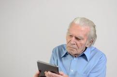 Uomo anziano che tiene un PC moderno della compressa Fotografia Stock