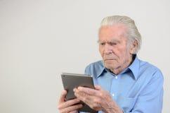 Uomo anziano che tiene un PC moderno della compressa Fotografie Stock Libere da Diritti