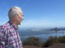 Uomo anziano che trascura il ponticello di cancello dorato fotografie stock