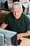Uomo anziano che utilizza computer nell'aula Fotografia Stock